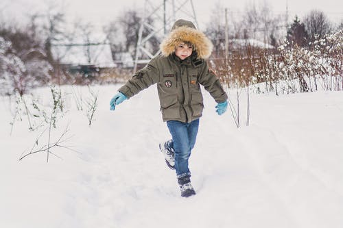 Child in Green Jacket and Blue Denim Jeans Standing on Snow Covered Ground