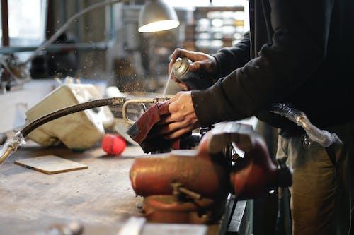 Unrecognizable male mechanic spraying metal detail in workshop