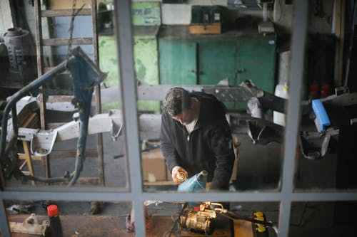 From window view of adult male worker in workwear standing at workbench and fixing metal detail while working in modern garage