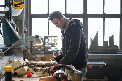 Serious bearded mechanic working at workbench in light workshop