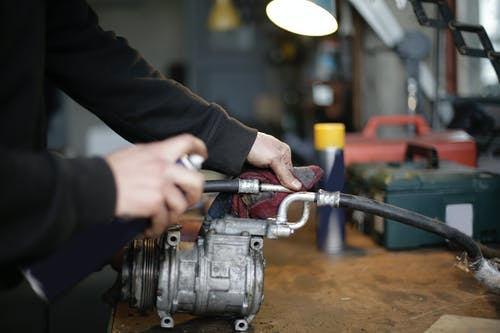 Unrecognizable crop mechanic fixing metal part on workbench in garage