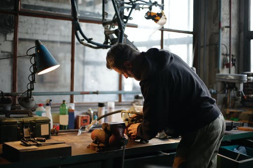Adult male worker fixing metal detail at workbench in workshop