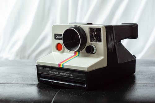 Vintage photo camera equipped with instant picture printer placed on leather surface against white curtain