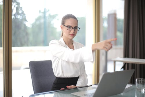 Serious businesswoman pointing away in office