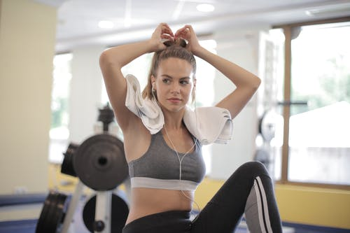 Concentrated female athlete wearing sportswear preparing for training while sitting with towel and looking away during break in fitness class
