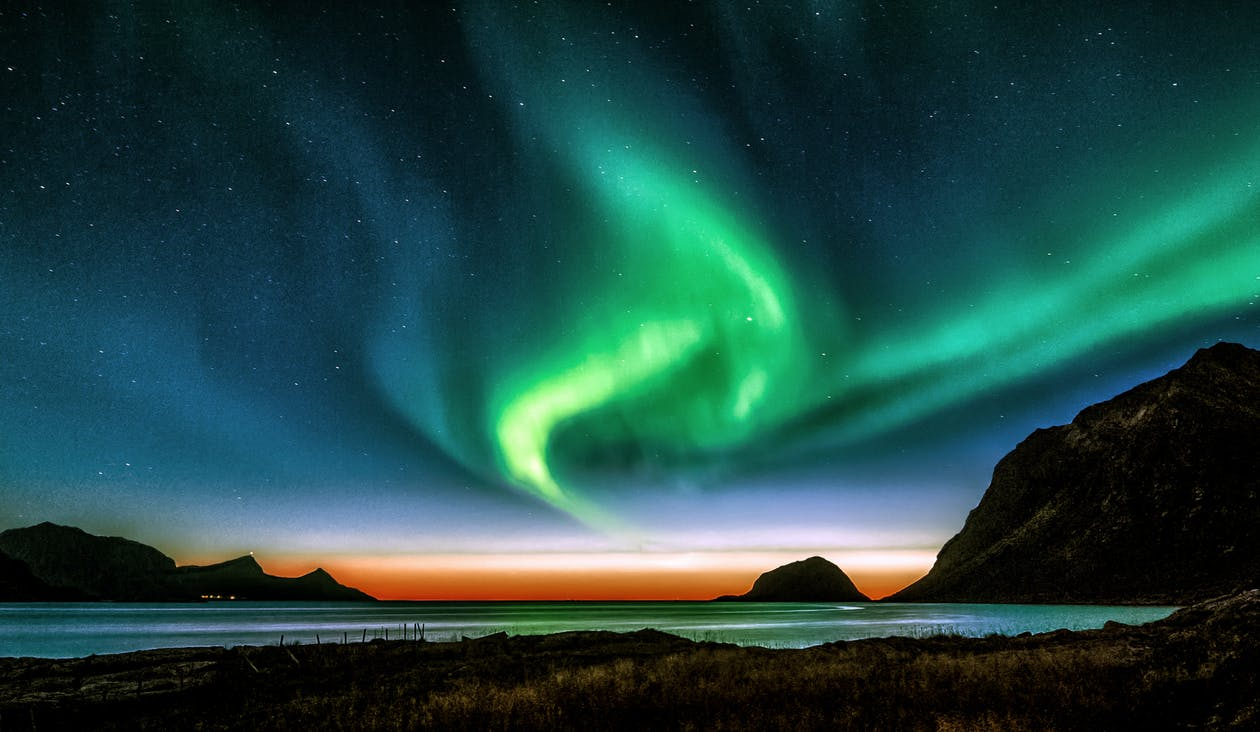 Green Aurora Lights over the Mountain during Night Time