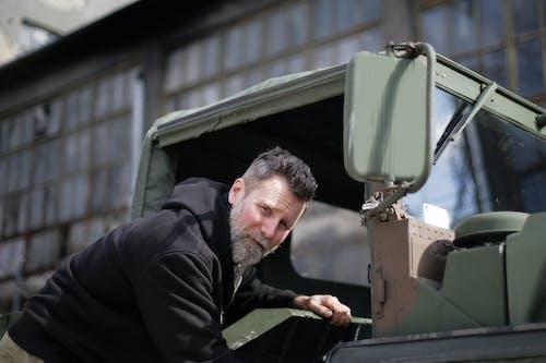 Bearded male mechanic fixing car on street near garage
