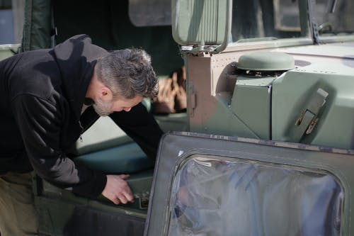 Side view of unrecognizable bearded mechanic in workwear standing near military car and checking details of seat while working on street near garage