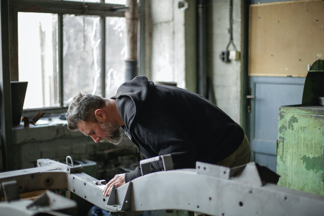 Focused bearded mechanic working with metal construction in garage