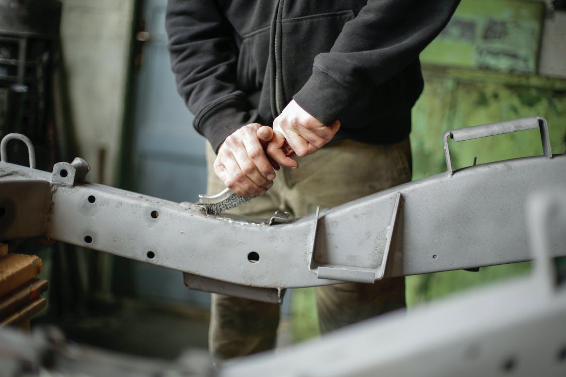 Unrecognizable crop mechanic working with metal details in garage