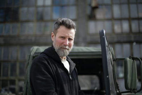Serious adult bearded man in casual clothes standing near open door of car on street near garage and looking at camera