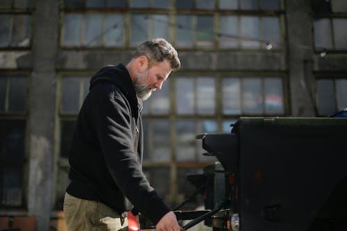 Focused bearded mechanic fixing metal details of car on street near garage