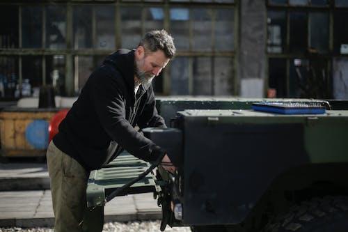 Adult bearded mechanic fixing metal part of car on street near garage