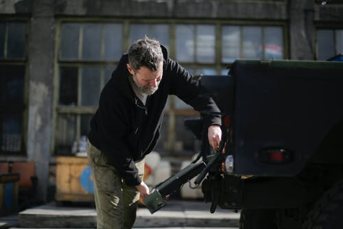 Serious adult bearded mechanic repairing metal door of car on street near garage