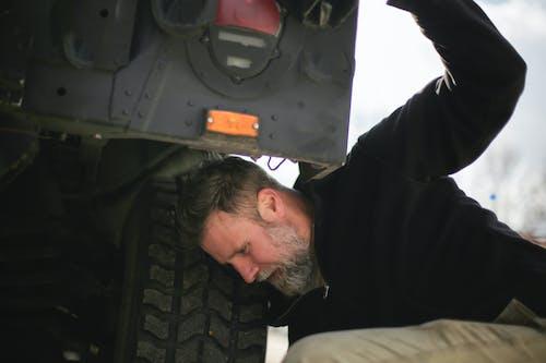 Adult bearded mechanic fixing car wheel on street