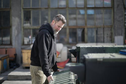 Side view of concentrated adult bearded mechanic in black workwear holding metal door of trunk while examining car on street near garage