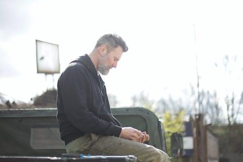 Serious bearded man sitting on metal platform on car outside garage