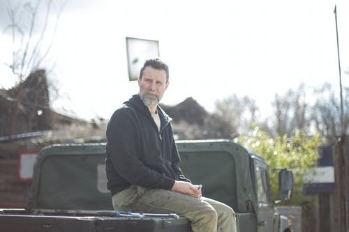 Man in Black Jacket Sitting on Car