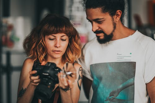 Man In White Crew Neck T-shirt Beside Woman Holding A Camera