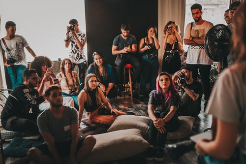 Group of multiethnic young people wearing casual clothes gathering together in spacious studio and listening attentively to female speaker