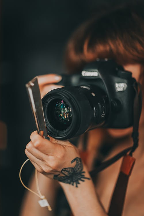 Crop unrecognizable female photographer with tattoo on hand taking pictures on professional photo camera against dark wall