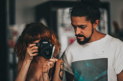 Female photographer taking photo on camera near ethnic tutor