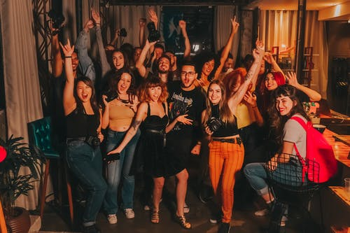 High angle of excited young diverse friends in casual outfits with arms raised yelling happily while celebrating project success in modern workspace