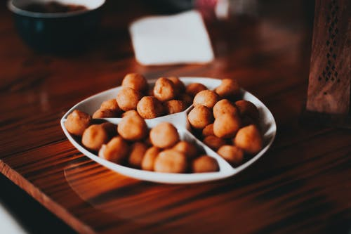 Roasted salty nuts on white plate served on table