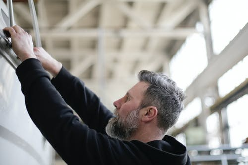 Side view of adult bearded mechanic in black workwear checking metal details while working in spacious modern hangar