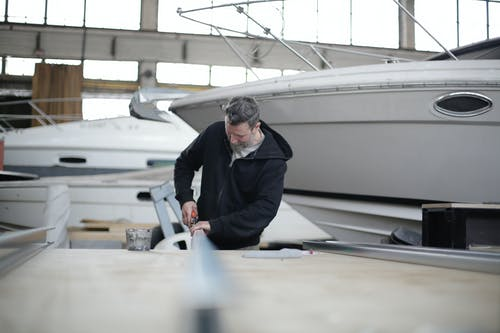 Serious adult bearded mechanic working with metal detail in hangar near motorboat