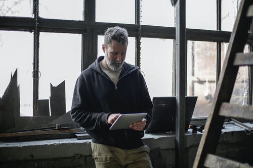 Serious adult bearded workman wearing workwear standing near window and browsing tablet while working in workshop