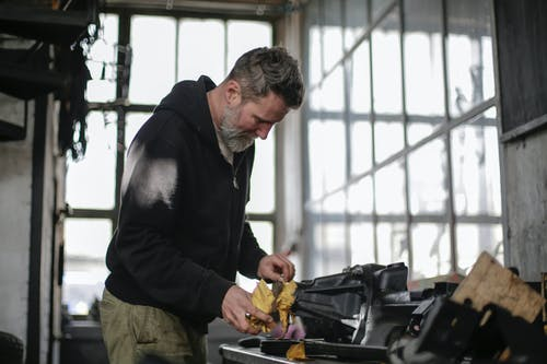 Serious adult bearded worker working with tools in workshop