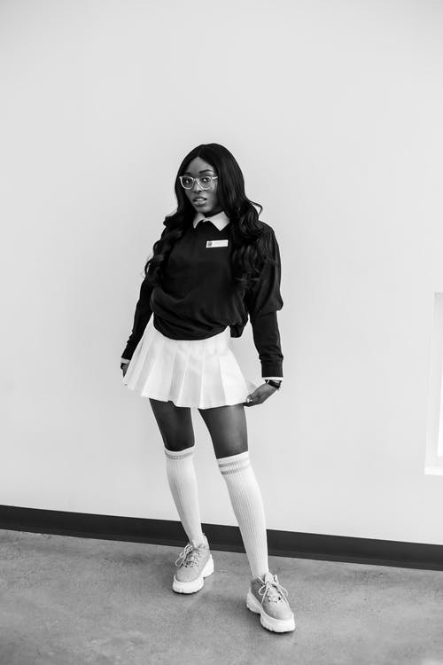 Full length of black and white African American female in trendy school uniform and eyeglasses standing near wall and looking at camera