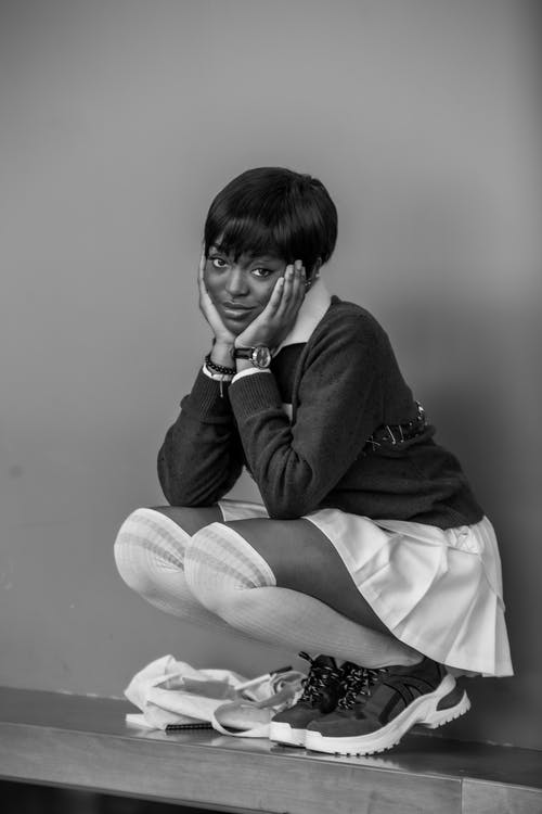 Black and white of positive young ethnic female with short hair in stylish outfit squatting near wall with hands on cheeks and looking at camera