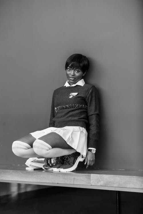 Stylish ethnic teen in short skirt and socks squatting near wall