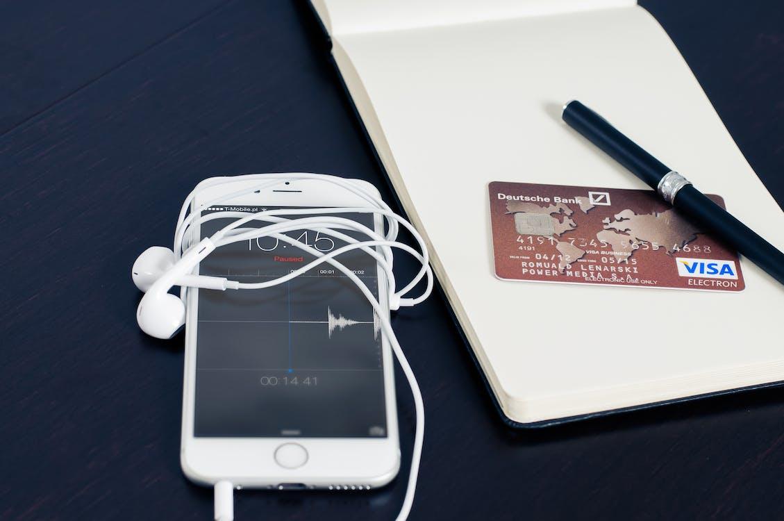 Silver Iphone 6 Beside Red Visa Card