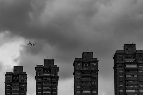 Aircraft flying in thick clouds above city buildings