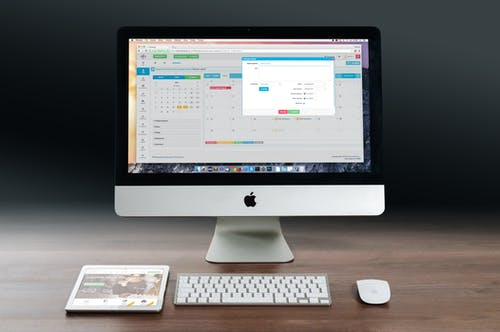 Silver Imac, Apple Magic Keyboard, and Magic Mouse on Wooden Table