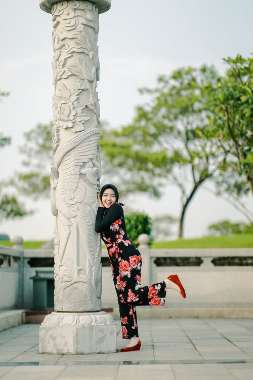 Sid view of happy young Asian female in casual clothes and headscarf leaning on carved column while having fun in park