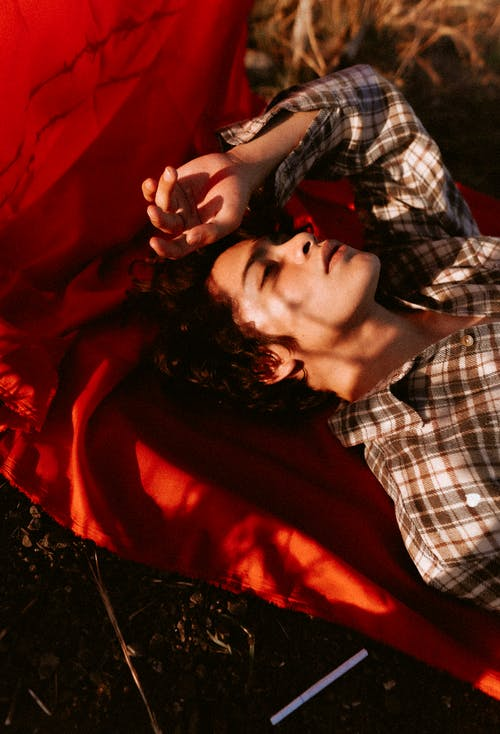 Tranquil young guy lying on blanket in field