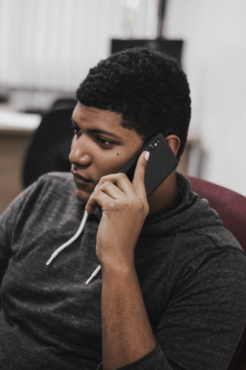 Thoughtful young man talking on smartphone in workplace