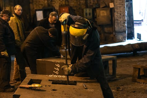 Unrecognizable male mechanic in protective mask and uniform working with metal construction using professional instrument in shabby factory