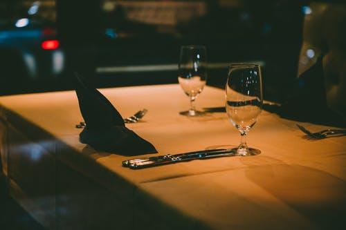 Clear Wine Glass Beside Silver Fork and Bread Knife on Table