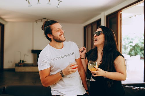 Cheerful young man and woman in trendy casual clothes standing near each other and laughing while drinking cocktails during meeting at home