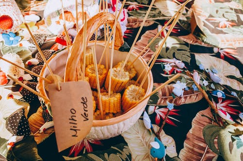 Assorted corn with wooden sticks in basket placed on tablecloth on table in market
