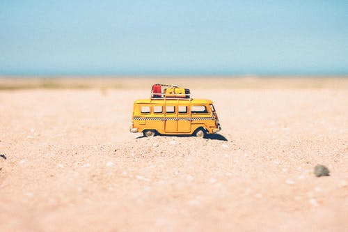 Yellow Die-cast Miniature Van on Brown Sand
