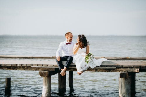 Bride and Groom Sitting on Wooden Dock