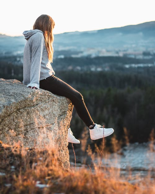 Woman in Gray Hoodie and Black Pants Sitting on Rock