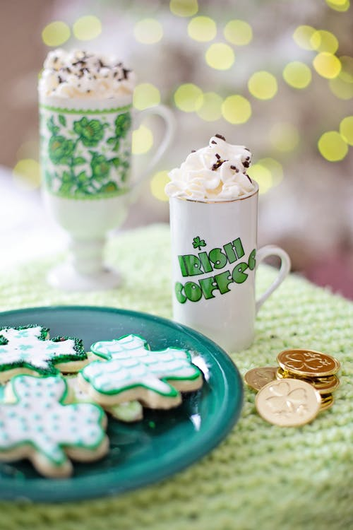 White and Green Ceramic Mugs Beside A Plate Of Cookies