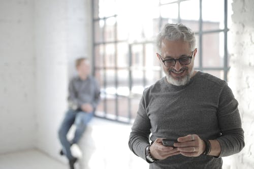 Mature man browsing smartphone in workplace